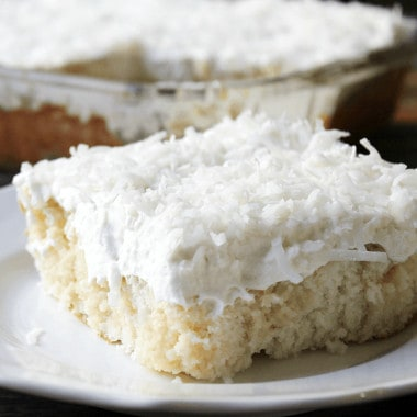 My Mom's Best Ever Coconut Cake is dessert heaven! Creamy, dreamy, tender cake topped with whipped cream is so easy to make and is loaded with coconut flavor!