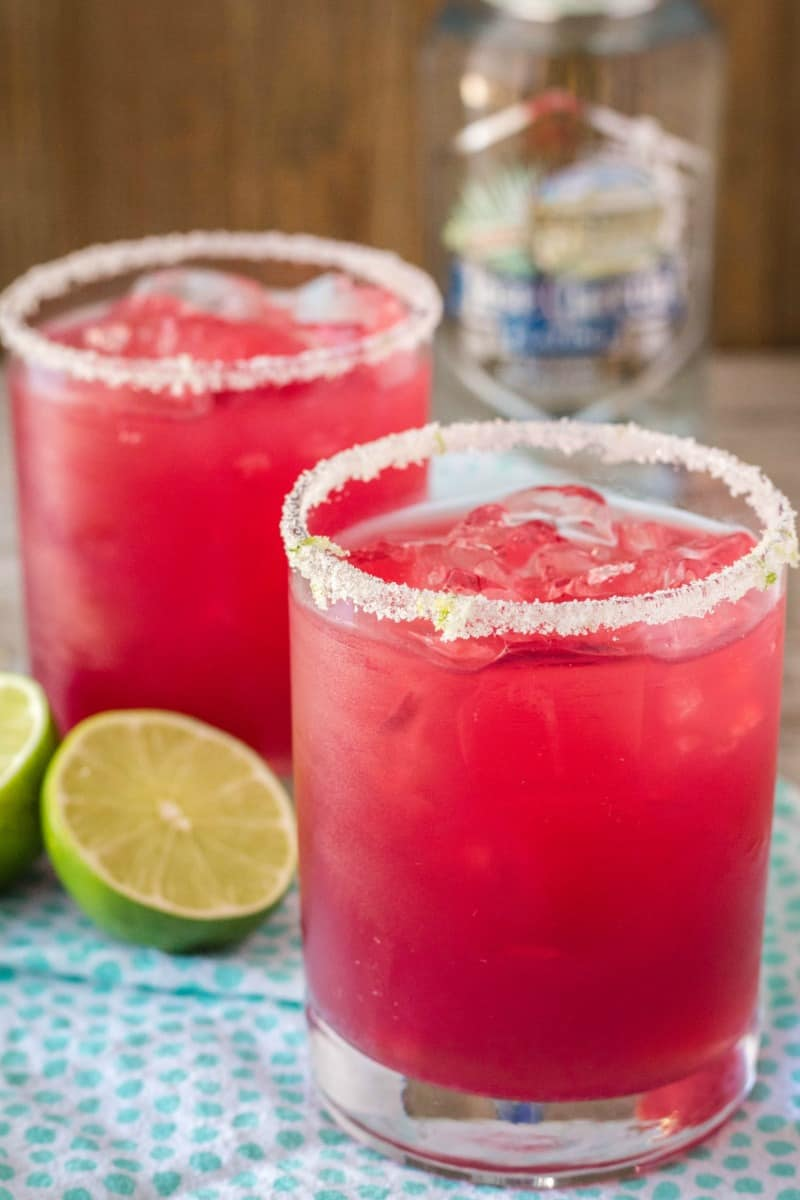 pomegranate margarita in a rocks glass with lime sugar