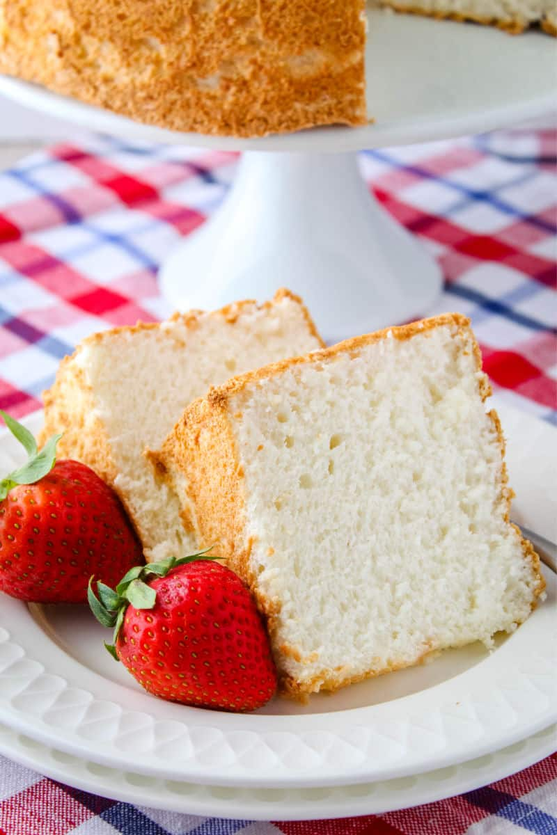 cloe up of two slices of angel food cake on a plate with strawberries