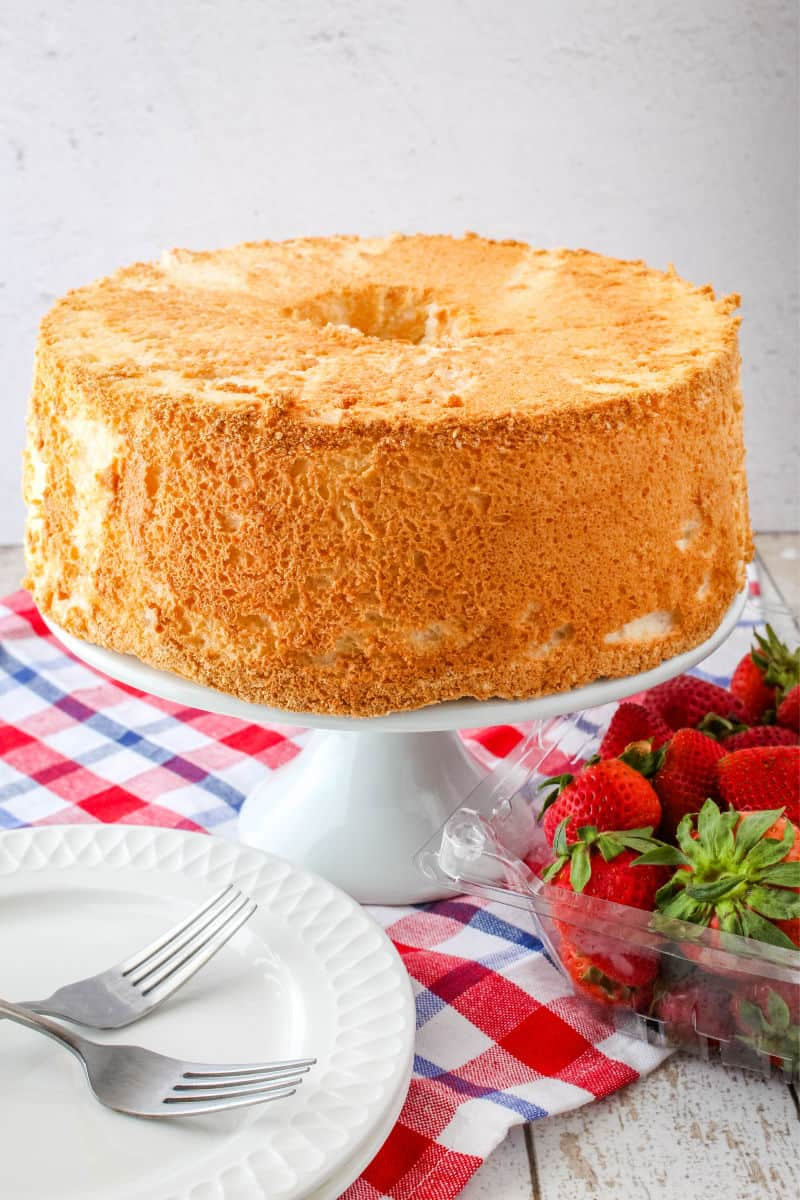 whole angel food cake on a cake stand next to plates, forks, and a bowl of strawberries