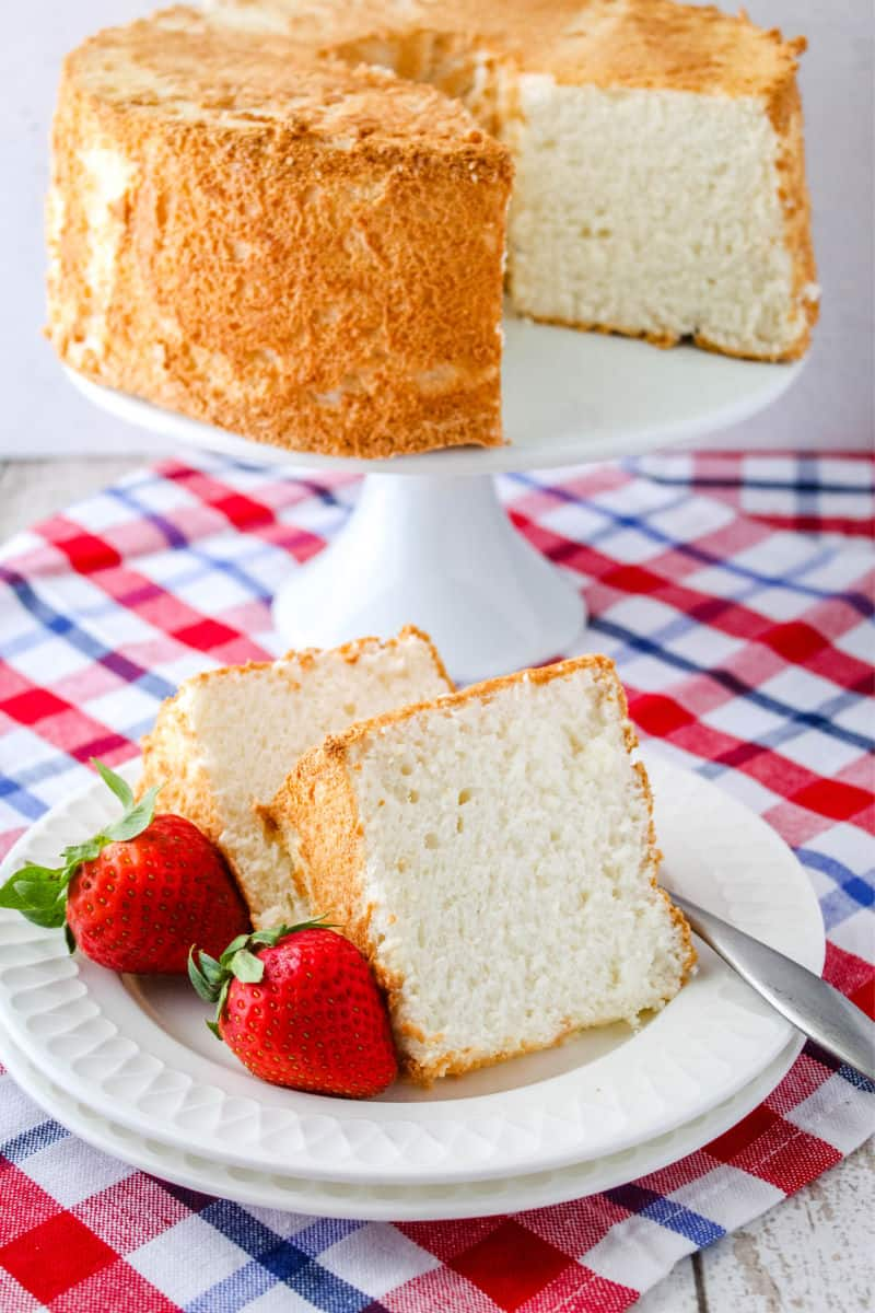 slices of angel food cake on a plate with strawberries and a fork with the rest of the cake behind them