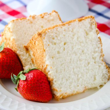 square image of two slices of angel food cake with two strawberries