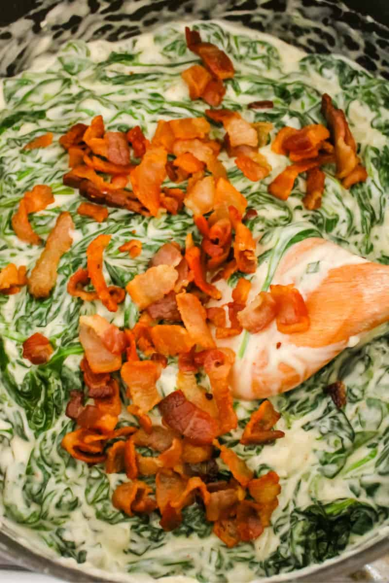 bacon being added to creamed spinach in a pot