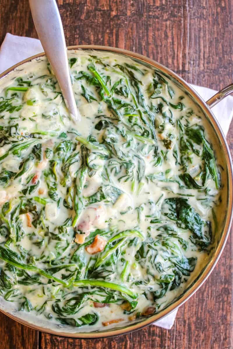 bowl of creamed spinach with a serving spoon