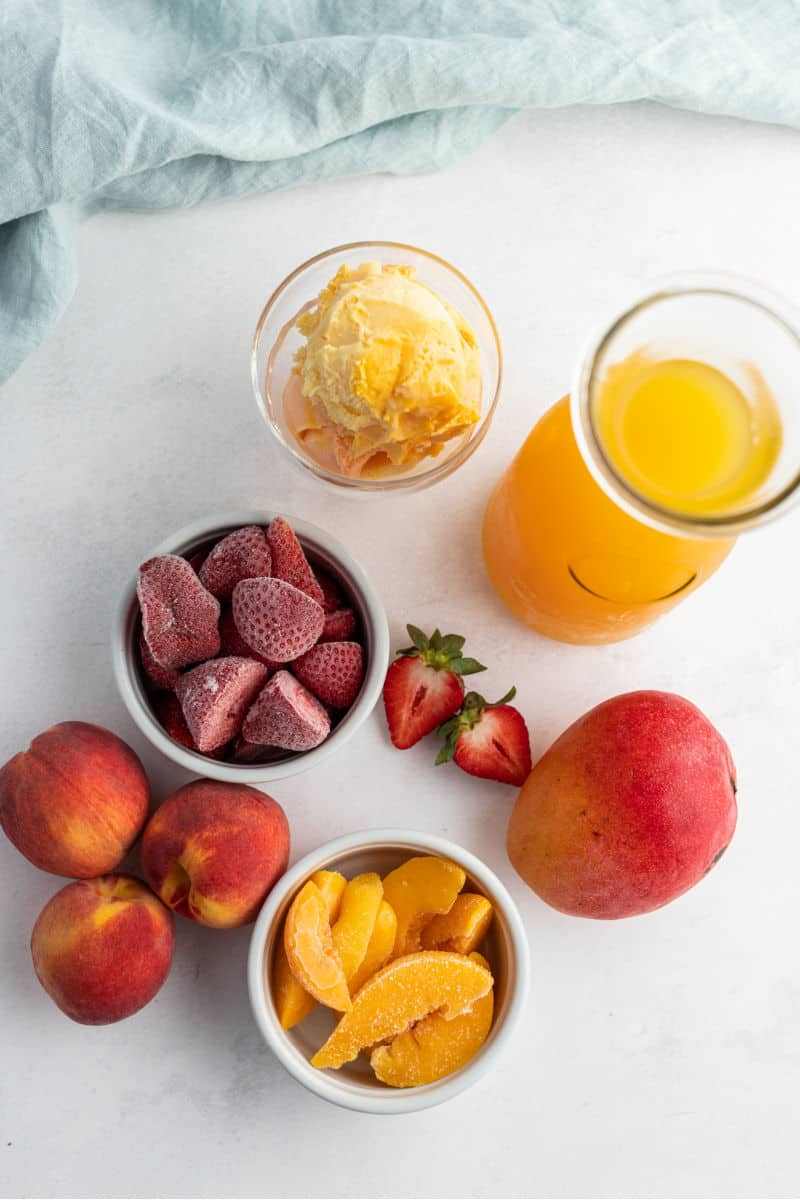 frozen strawberries in a bowl, frozen peaches in a bowl, orange sherbet scoops in a bowl, mango juice blend in a carafe