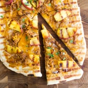 Grilled BBQ Pulled Pork & Peach Gourmet Pizza Recipe is one of those bites of food bliss you just can't stop eating! I love the combination of luscious, fatty pork with fresh peaches and cilantro!
