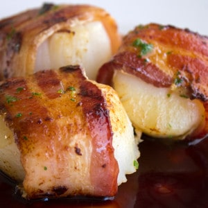 Bacon Wrapped Scallops Recipe with Pomegranate Sauce are a succulent dish that's fancy enough for a dinner party, or serve them family style for your friends!