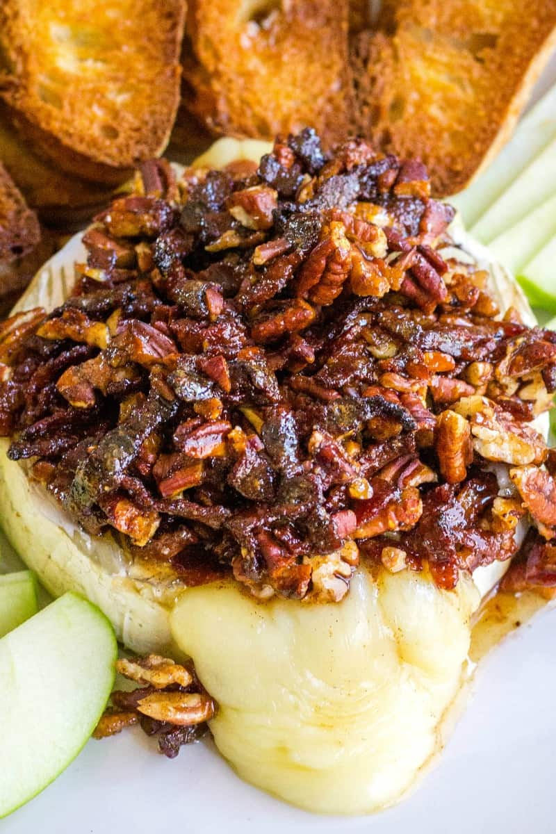 baked brie topped with pecans and bacon in a spiced honey sauce