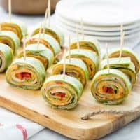 Roasted Red Pepper Hummus Pinwheels with toothpicks lined up on a cutting board
