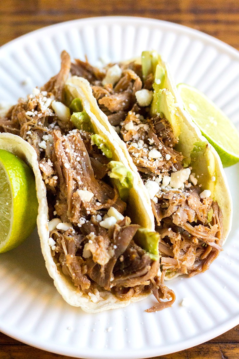 Slow Cooker Carnitas tacos with avocado and cojita cheese