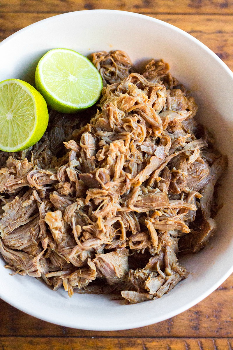 Cuervo & Tecate Slow Cooker Carnitas shreded in a serving bowl with limes