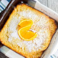 orange ricotta dutch baby dusted with powdered sugar and an orange slice