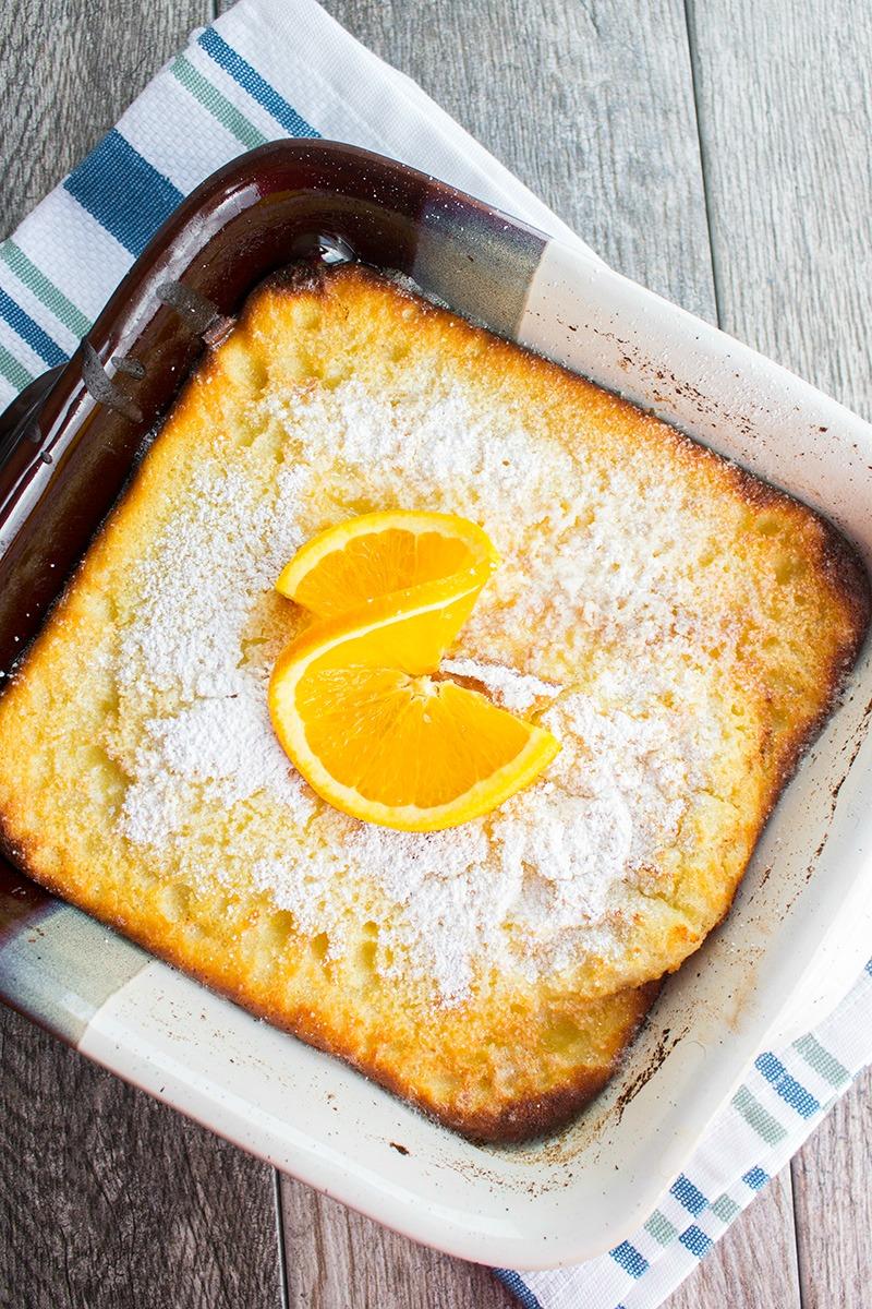 orange ricotta dutch baby dusted with powdered sugar and an orange slice