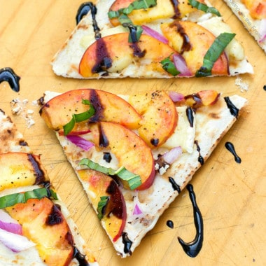 Entertaining doesn't get easier than making this Peach & Brie Flatbread Recipe & opening a bottle of wine! This appetizer is always a hit with our friends!