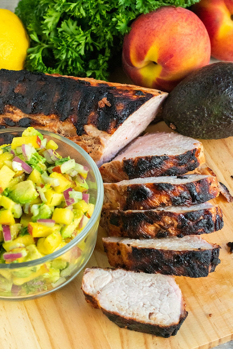 grilled pork tenderloin partially sliced alongside a bowl of avocado peach salsa