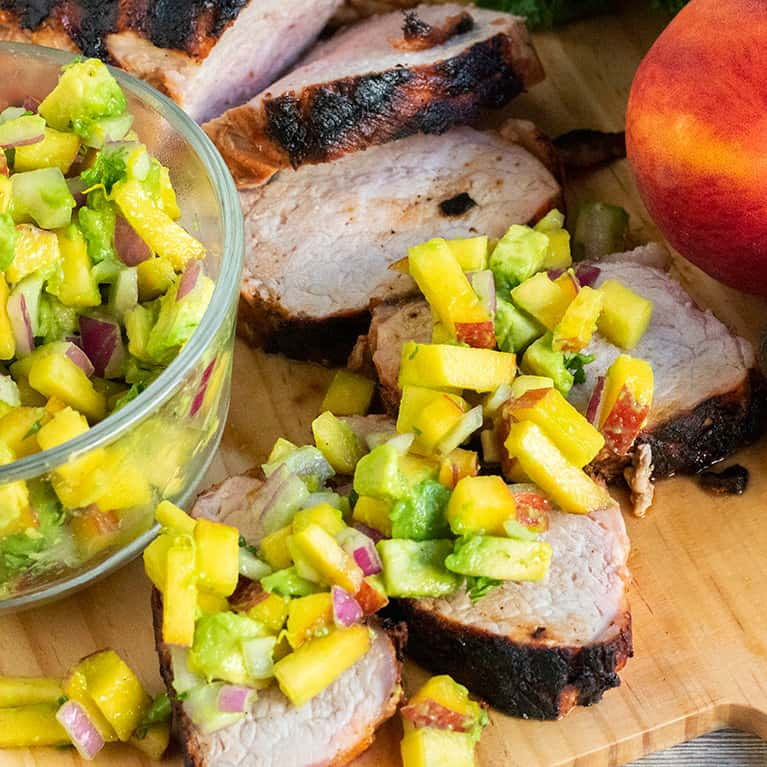 Grilled Pork Tenderloin with Avocado Peach Salsa is bursting with flavor! This easy grilling recipe will leave a smile on your face and full bellies all around!