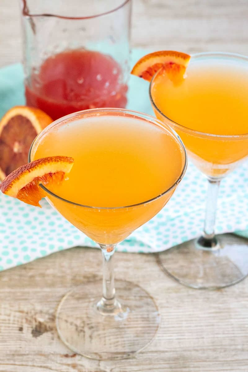 sparkling blood orange cocktail in coupe glasses with glass of mix behind