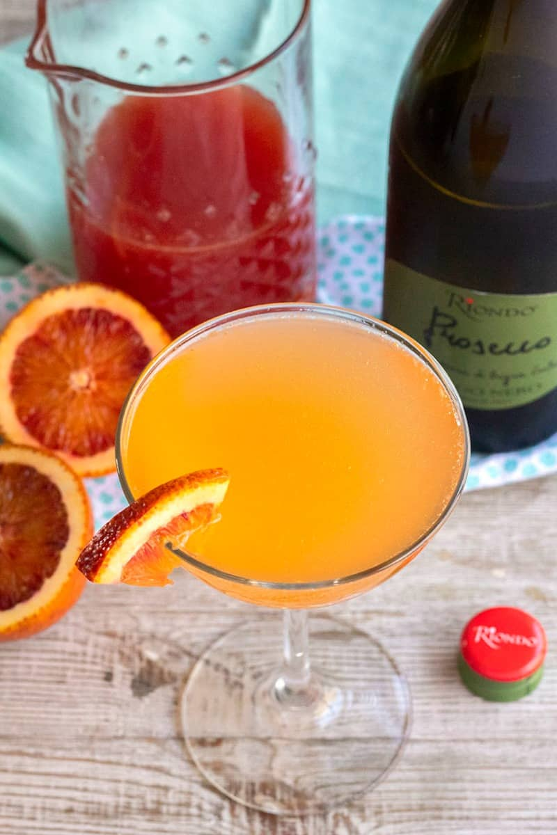 sparkling blood orange cocktail on glass with mix and prosecco bottle