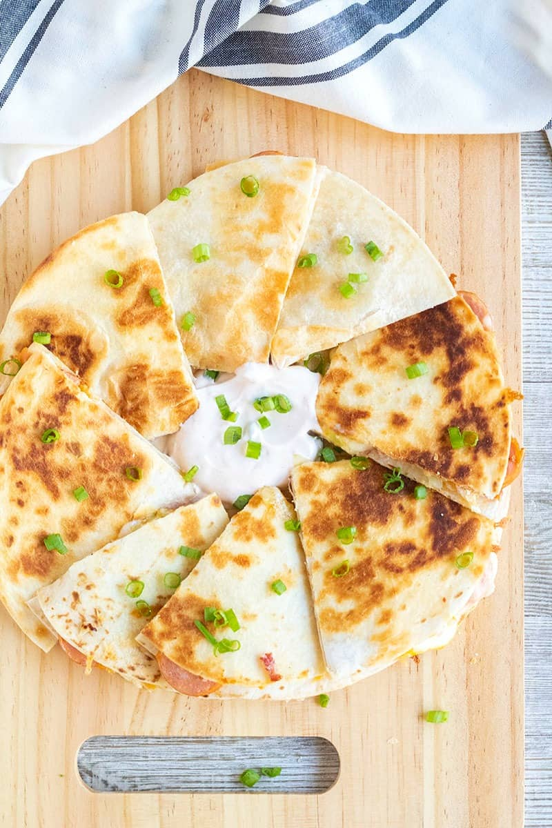 chipotle polish saqusage quesadillas cut into pieces and served with chipotle sour cream