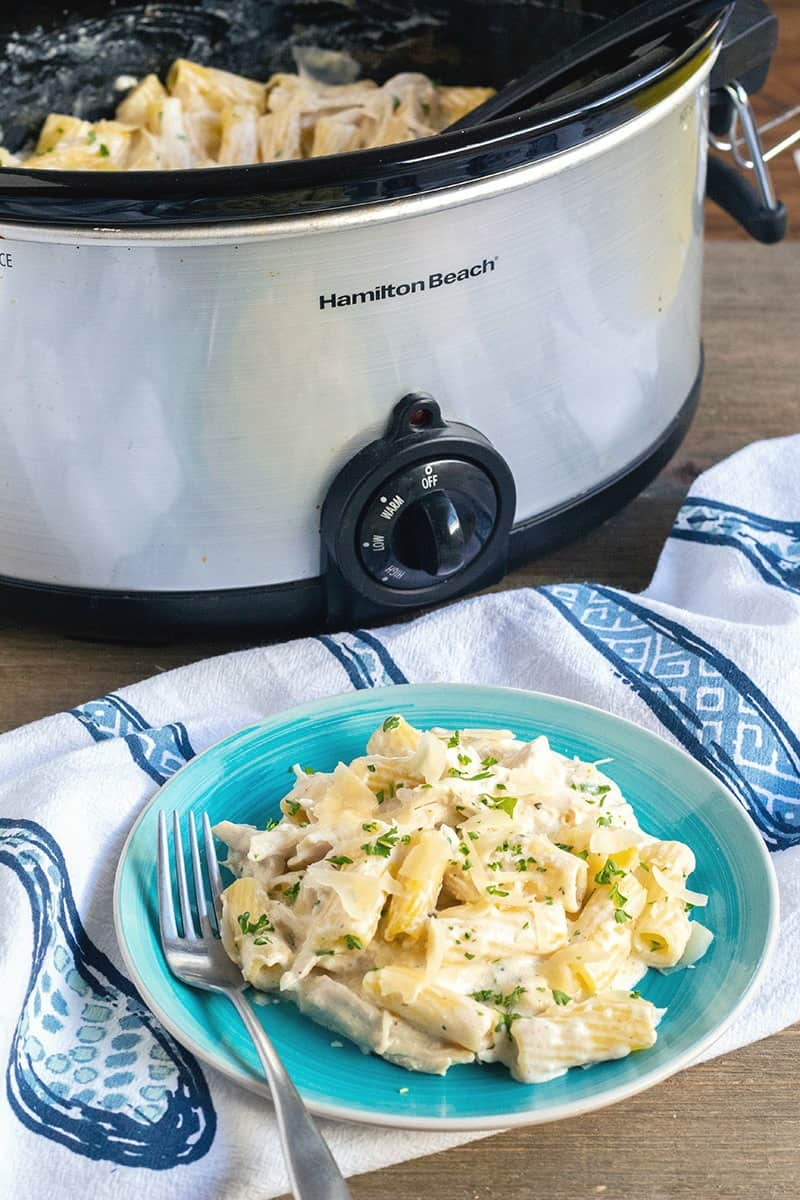 Crock Pot Chicken Alfredo served on a plate with crock pot behind it