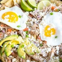 cast iron skillet filled with Pork Chilaquiles with eggs