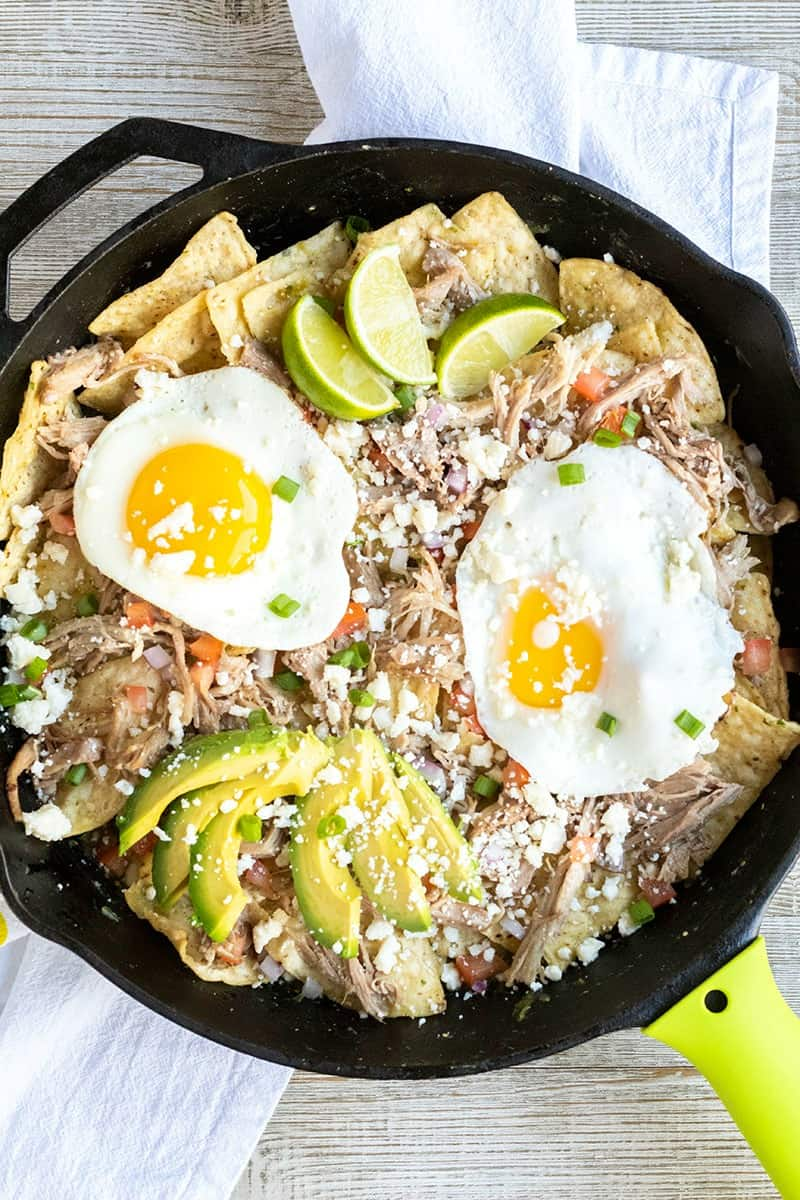 skillet of pork chilaquiles recipe garnished with queso fresco, onion, tomato, avocado, and lime