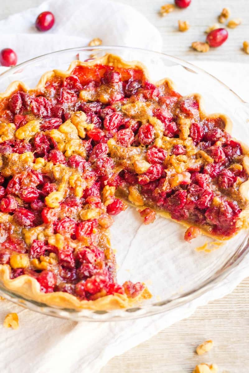 cranberry pie in a pie plate with a slice taken out