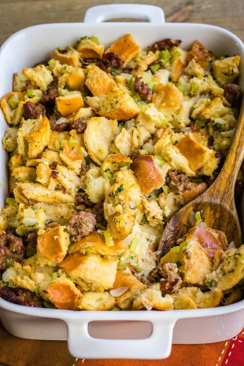 sausage stuffing in a baking dish with a serving spoon