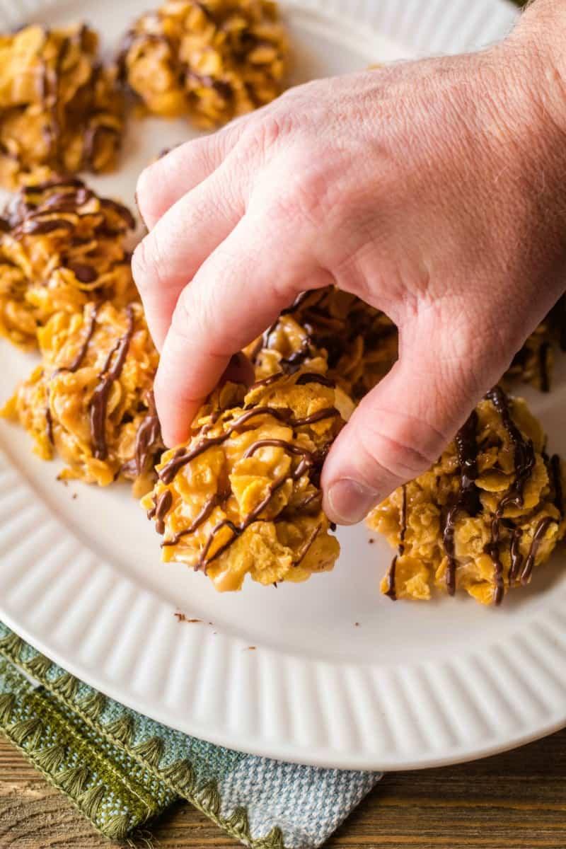 hand grabbing a peanut butter cornflake cookie off a platter