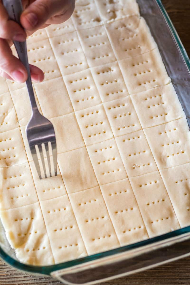 holes being poke into the top of scottish shortbread cookies