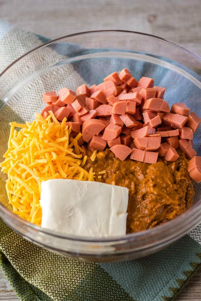 ingredients to make chili cheese dog dip in a mixing bowl