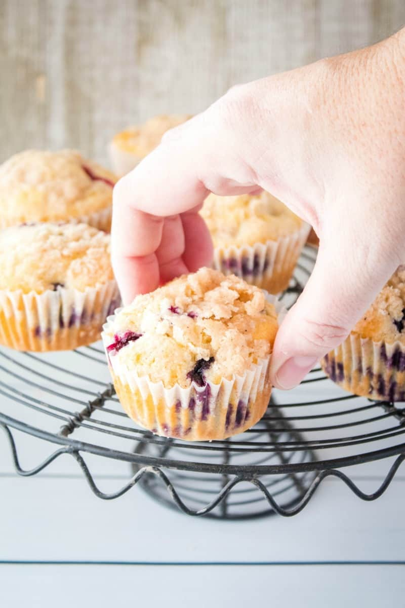 hand picking up a blueberry muffin from a cake stand