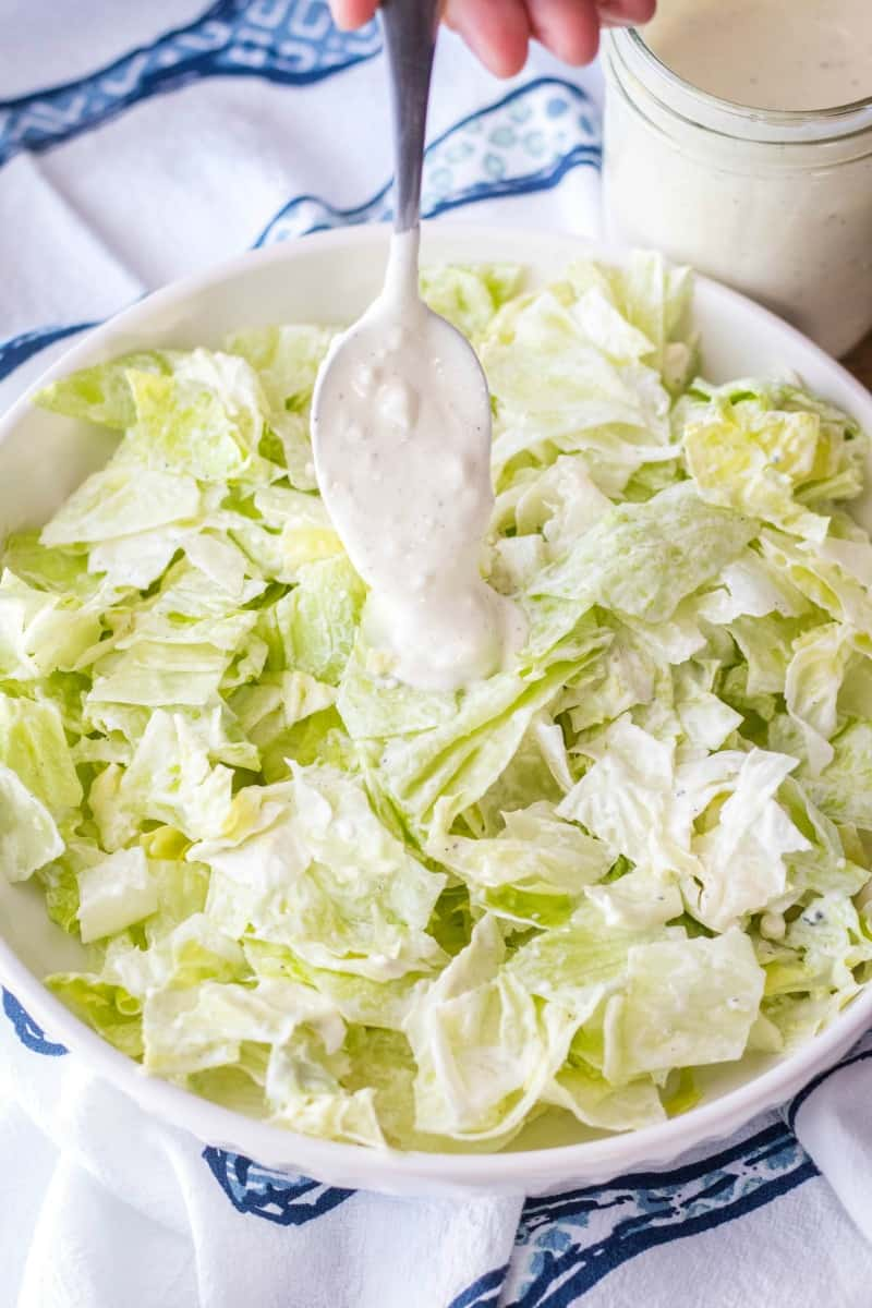 spooning blue cheese dressing onto lettuce