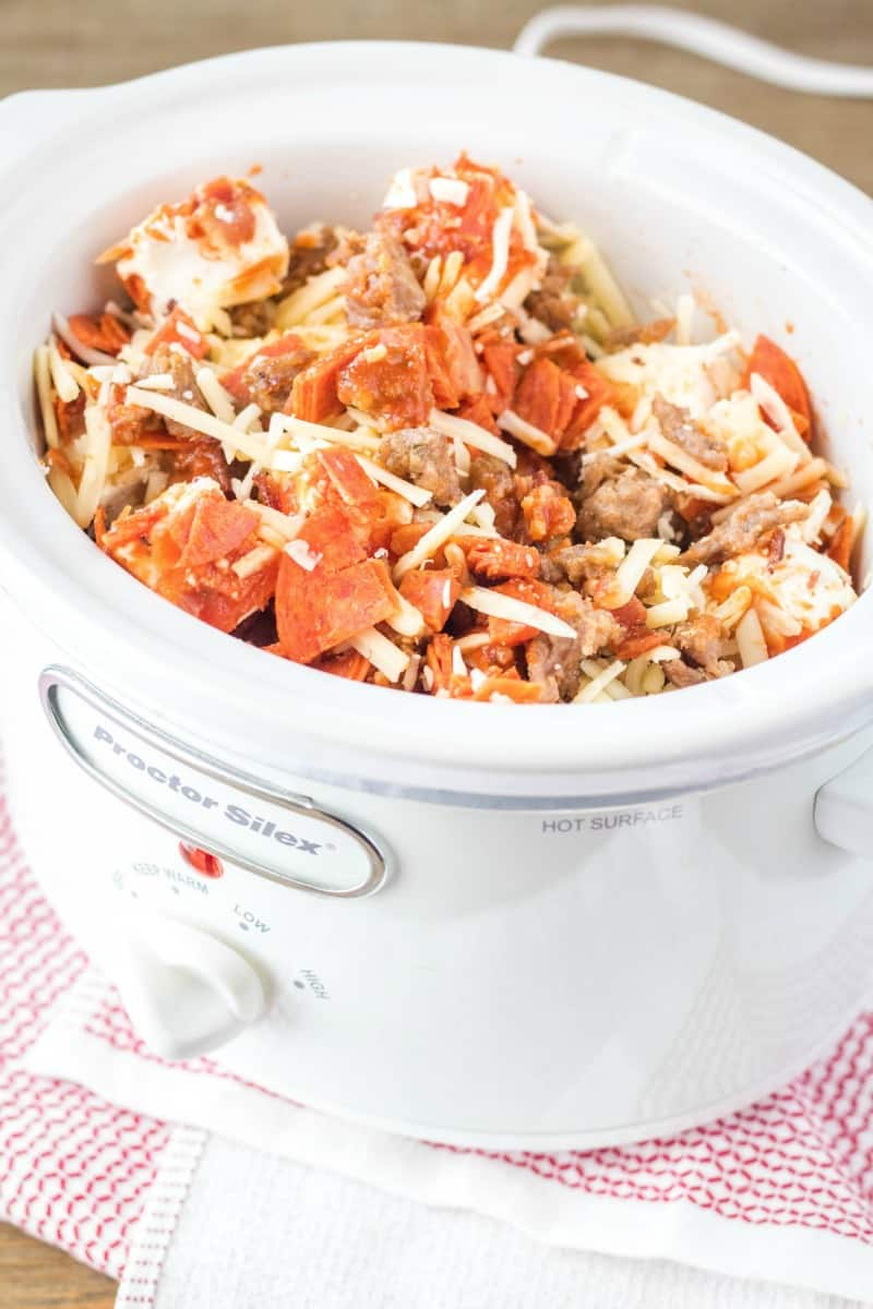 ingredients for crock pot pizza dip in a slow cooker