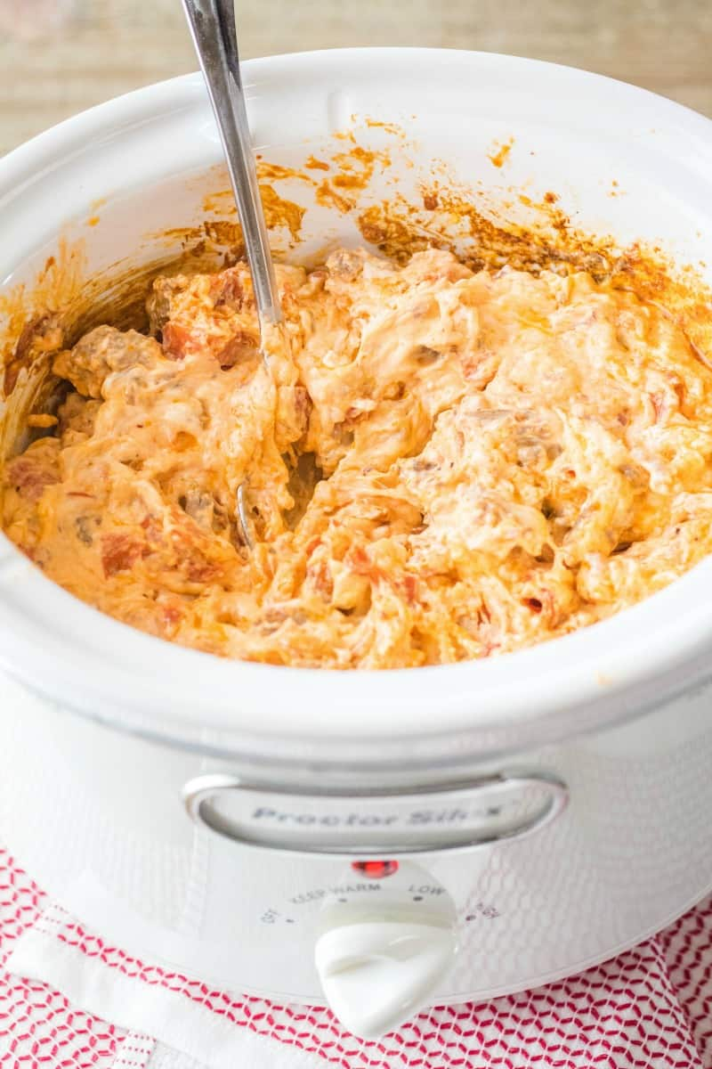 meat lover's crock pot pizza dip with a spoon