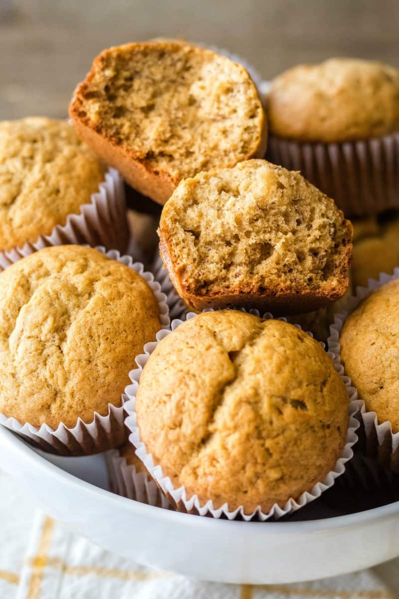 banana bread muffins piled in a bowl with one broken open to show inside