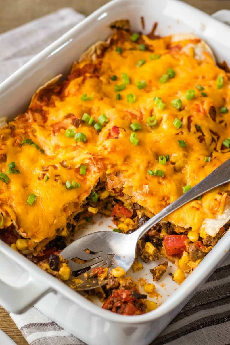 mexican lasagna in a baking dish with a portion taken out