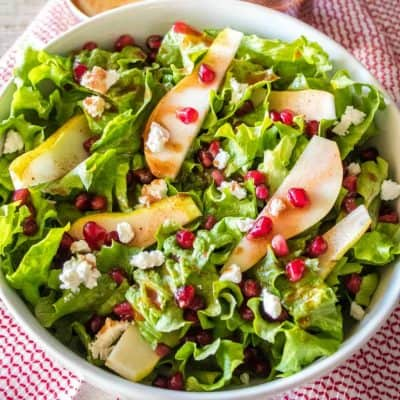 Craving a yummy salad? This easy Pomegranate and Pear Salad is drizzled with pomegranate vinaigrette and studded with goat cheese. It's great all by itself or topped with grilled chicken!