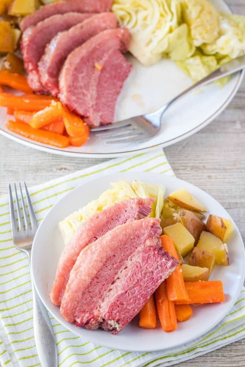 corned beef and cabbage on a dinner plate with a fork and napkin