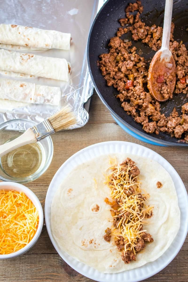 tortillas being filed with spicy ground beef and cheese for baked beef taquitos