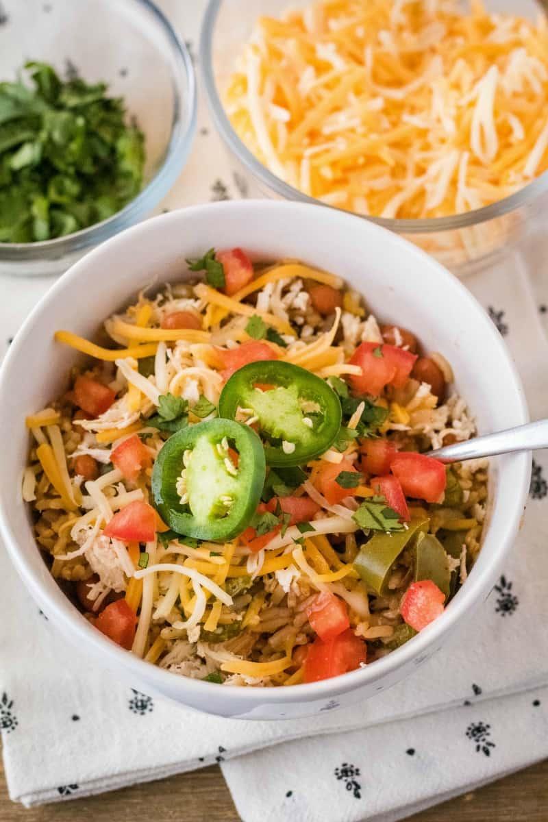 instant pot fajita burrito bowl topped with bowls of cheese and cilantro