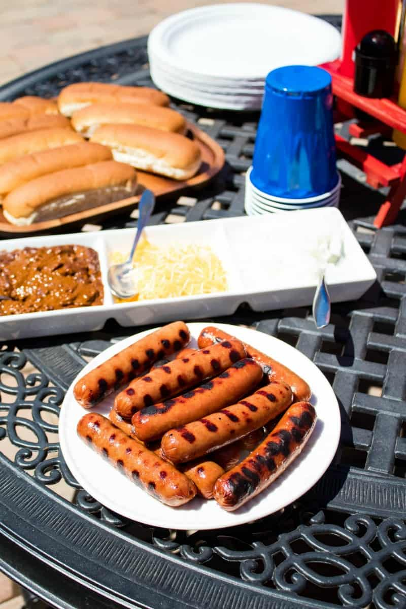 hot dogs, hot dog buns, and chili dog toppings on a patio table