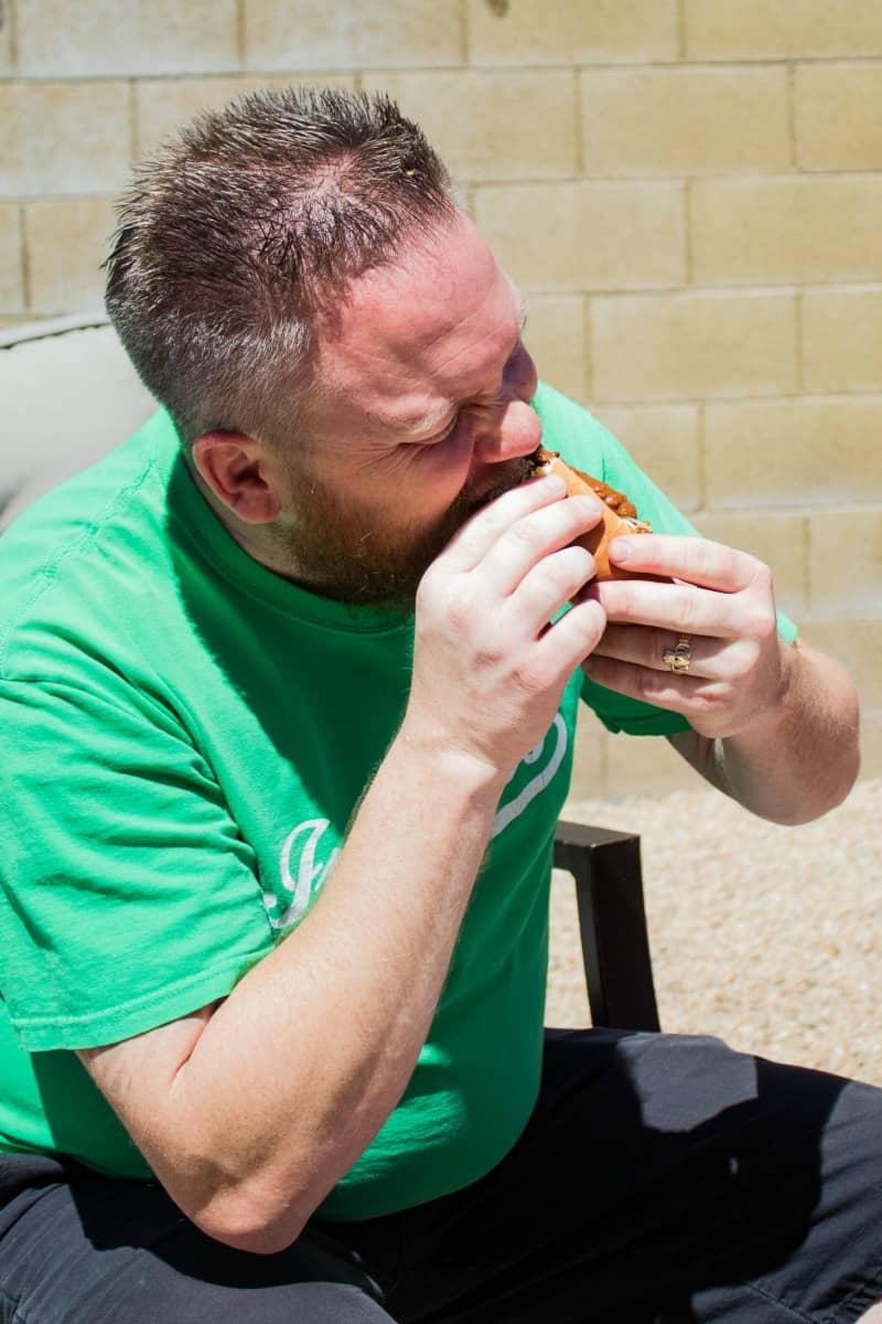 man taking a bite of a chili dog