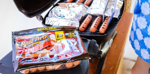 woman grilling hot dogs and foil packets on grill