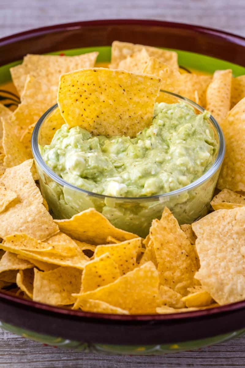 chip in a bowl of guacamole dip
