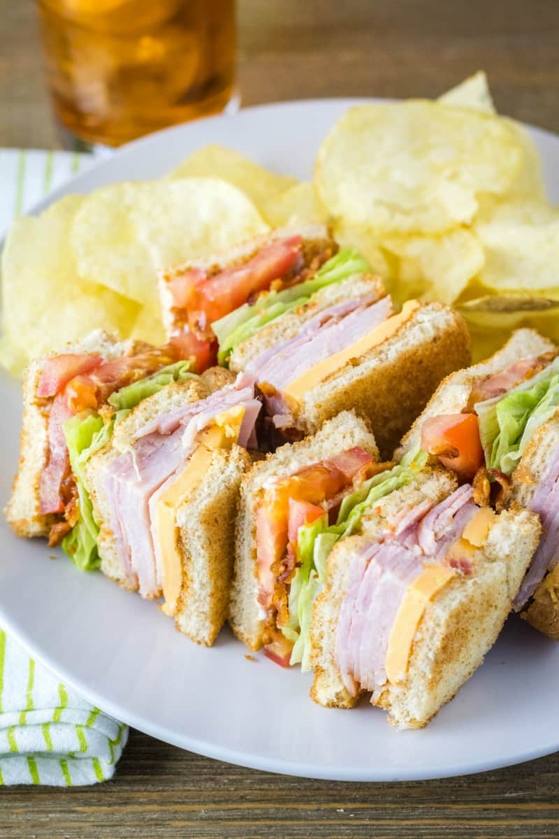 club sandwich cut into quarters laying on a plate with chips
