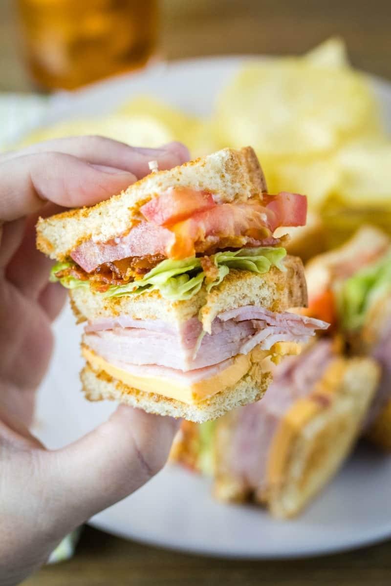 hand holding a club sandwich quarter