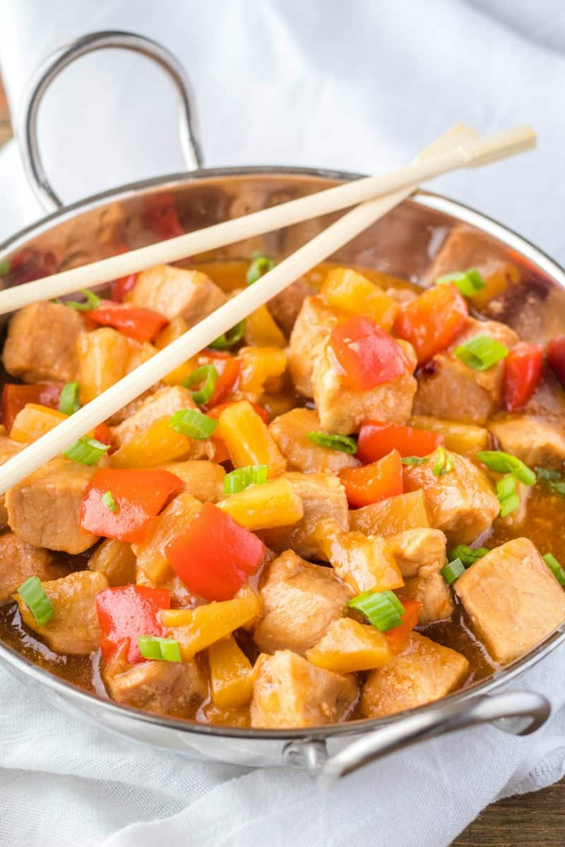 sweet & sour pork in a serving bowl topped with green onion