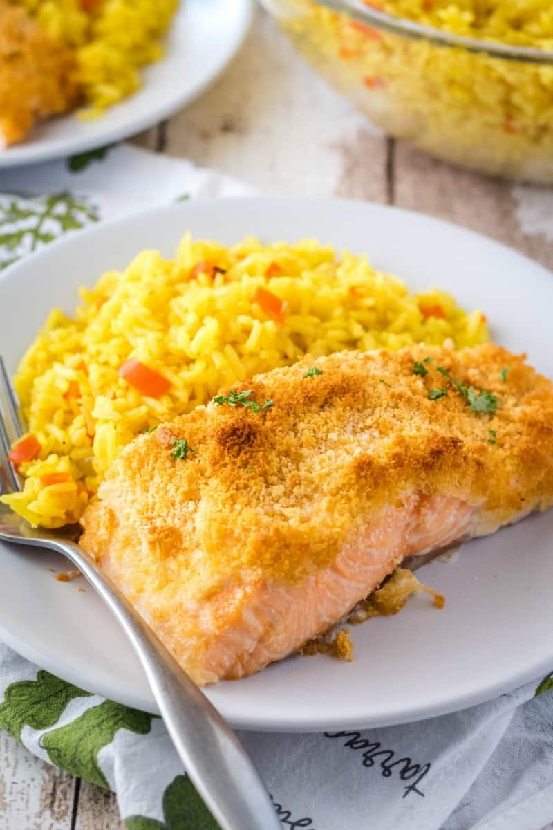 portion of parmesan ccrusted salmon on a plate with rice pilaf