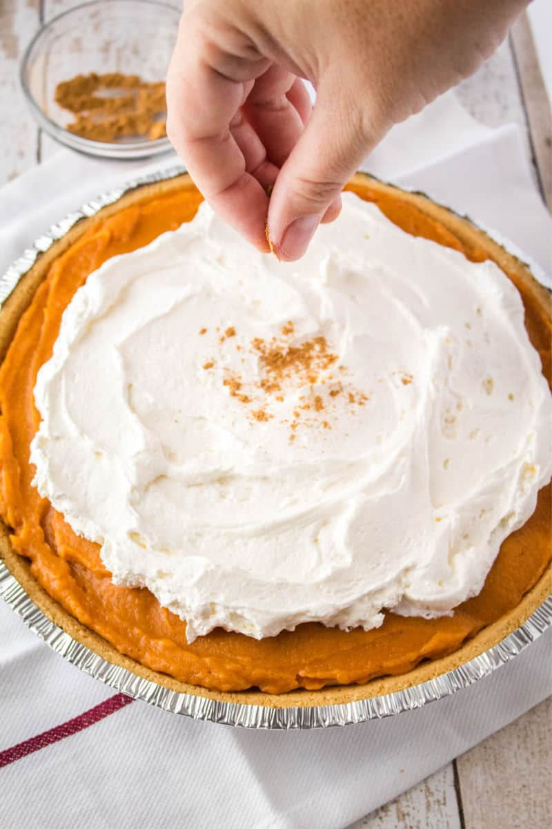 chai spice being sprinkled on top of cream cheese pumpkin pie